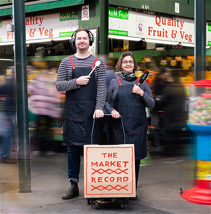 Two people stand with a shopping trolley, one with a microphone and one with a wooden spoon in hand. On the trolley a sign reads