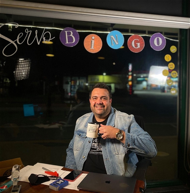 Comedian Dane Simpson is sitting in the window of a pub drinking from a mug. He is looking directly at the camera and smiling. He wears a denim jacket over a black shirt, and has a silver wristwatch on. On the table in front of Dane is a laptop, a mobile phone, a kazoo, some playing cards, a face mask, hand sanitiser, and pens and paper. On the window there is a colourful decal that says