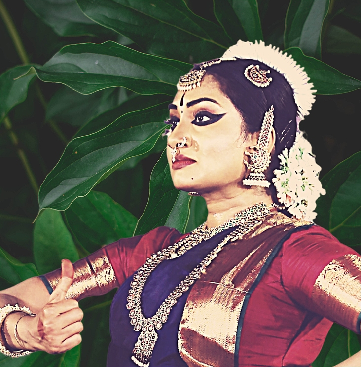 A woman in Red and purple Indian Bharathanatyam costume , holding Shikara hand gesture on Right hand. Green mango leaves in the background.