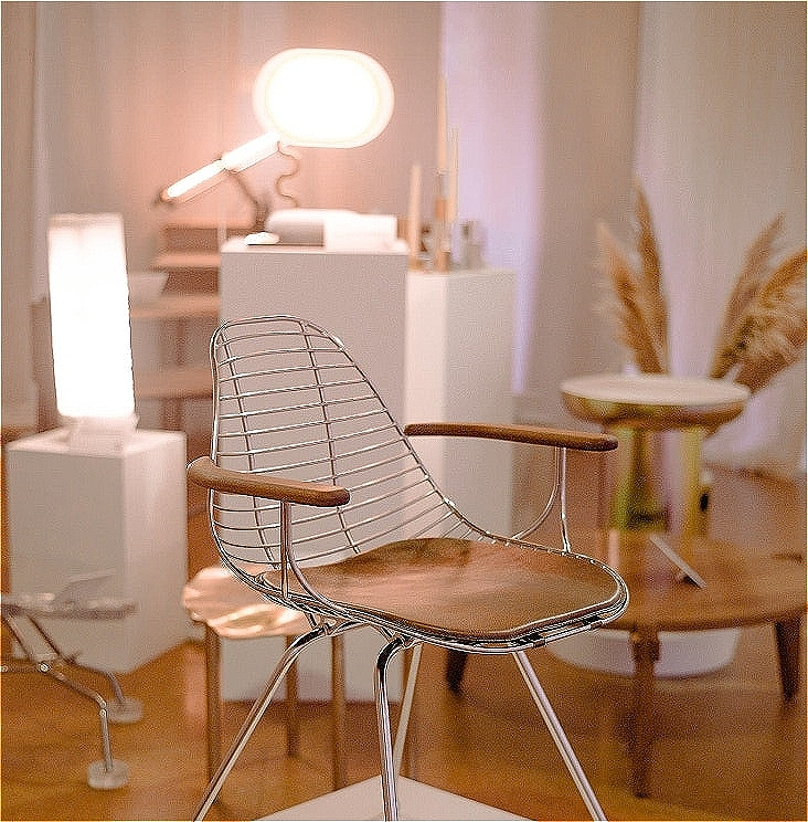 A view of an exhibition with a silver chrome and brown timber and brown leather chair in the foreground. There are a number of out of focus objects in the background including two lamps sitting on white plinths.