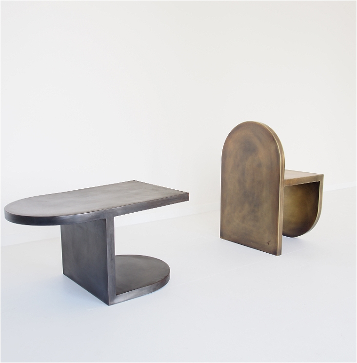 Two chairs are in this image, against a white background. The chair on the left is silver and has no back. It has one rounded side and one square side. The chair on the right is bronze and has a rounded back.