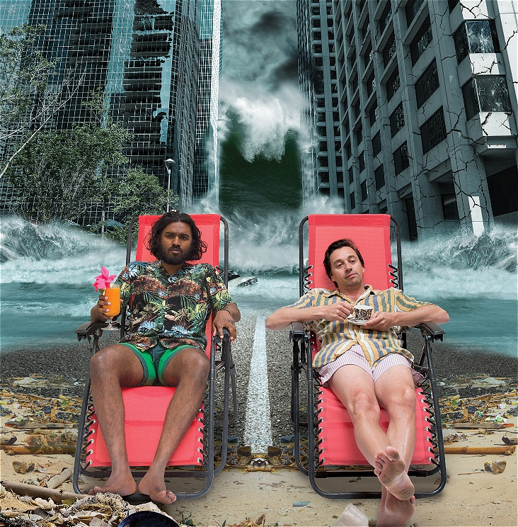 Two men are sitting on deckchairs on a beach surrounded by rubble. There is a Tsunami wave and two tall skycraper buildings on either side of them. The sky looks dark and ominous. The man on the left is holding a cocktail. The man on the right is half asleep and holding a tea cup.