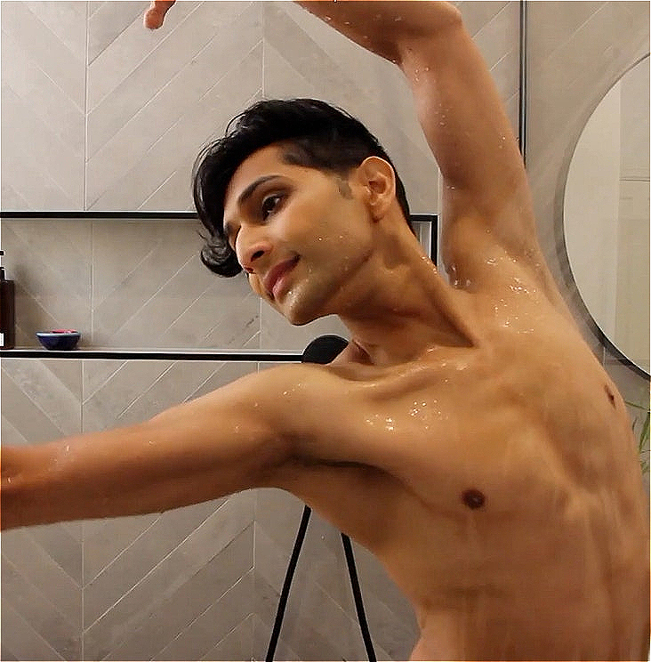 Artist Govind Pillai stands in a running shower shirtless with arms akimbo. Behind them is grey tiles with black shelving and a circular mirror